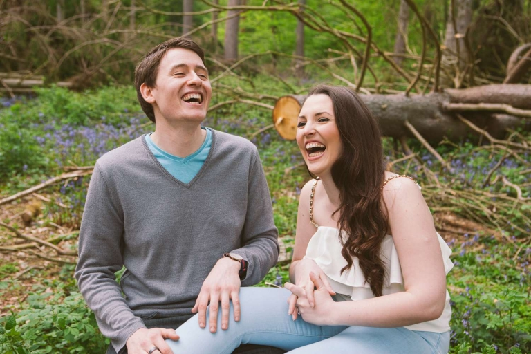Couple laugh during bluebell engagement shoot