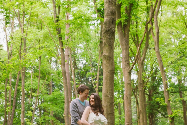 Couple stood amongst the trees in engagement shoot