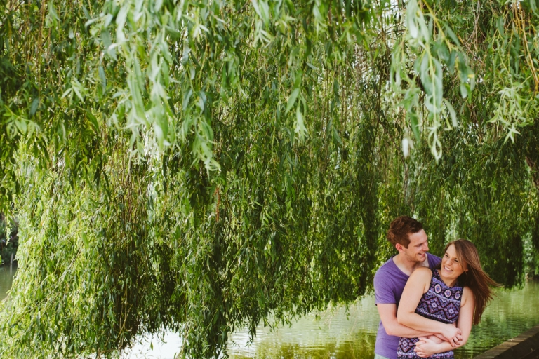 Couple hug under willow tree during engagement shoots