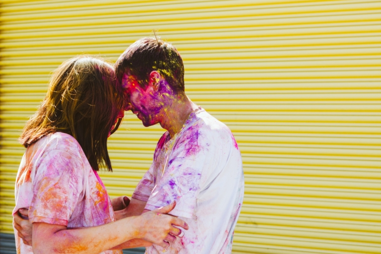Couple covered in paint after paint fight during engagement shoots