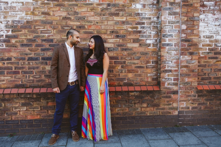 Couple stood by wall during London engagement shoot