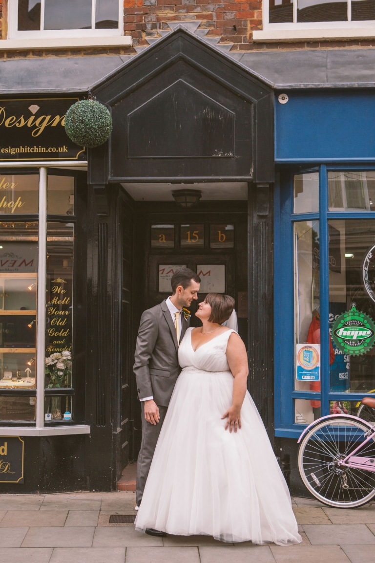 Couple Posed Outside Shops During Hitchin Wedding