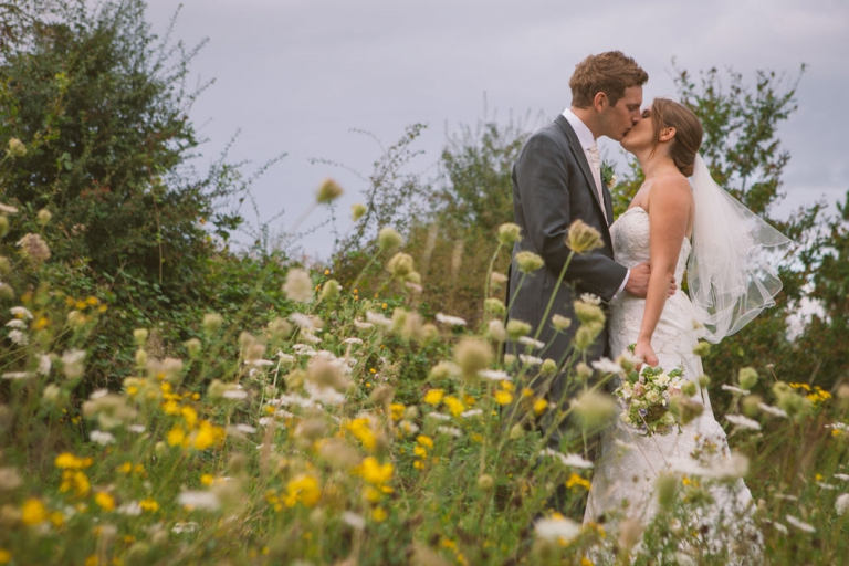 Couple kiss stood in wildflowers at Essendon Country Club wedding
