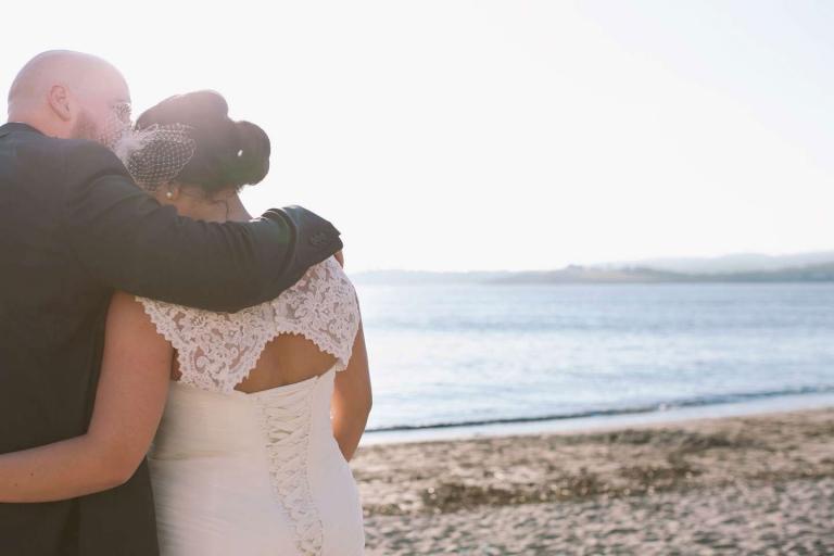 Groom hugs bride on beach at Cornwall beach wedding