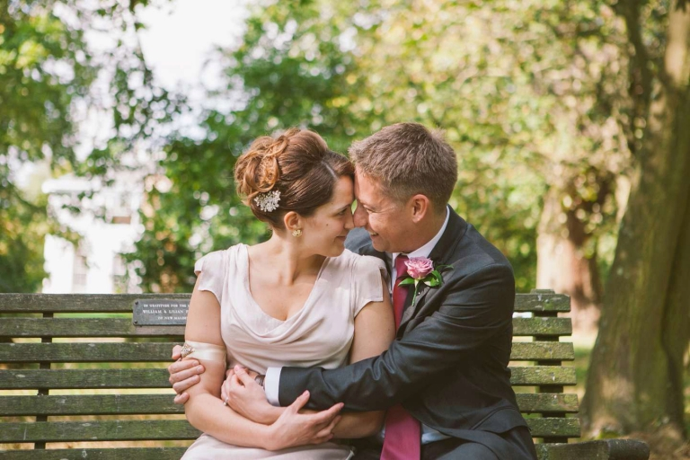 Couple sat on bench at Pembroke Lodge wedding