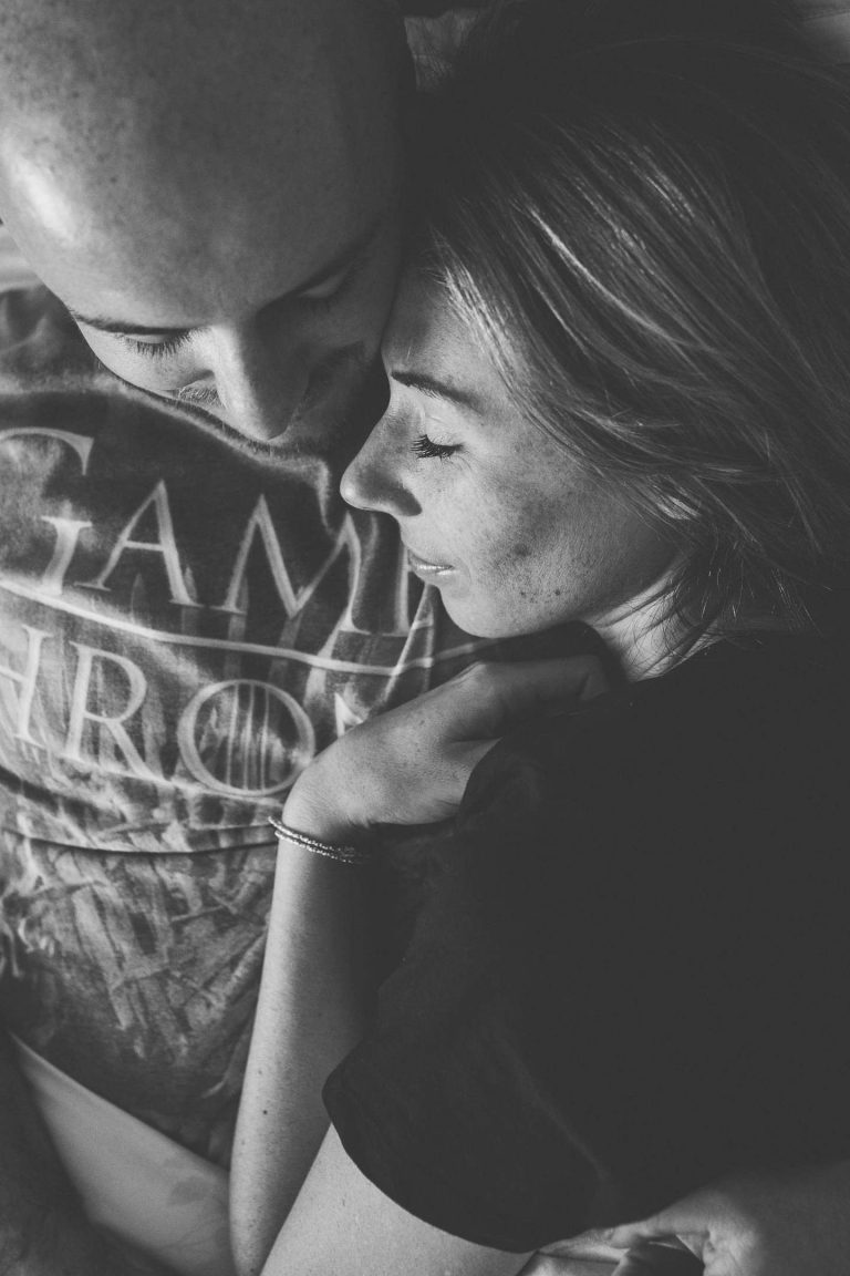 Couple cuddle in bed during Watford home engagement shoot