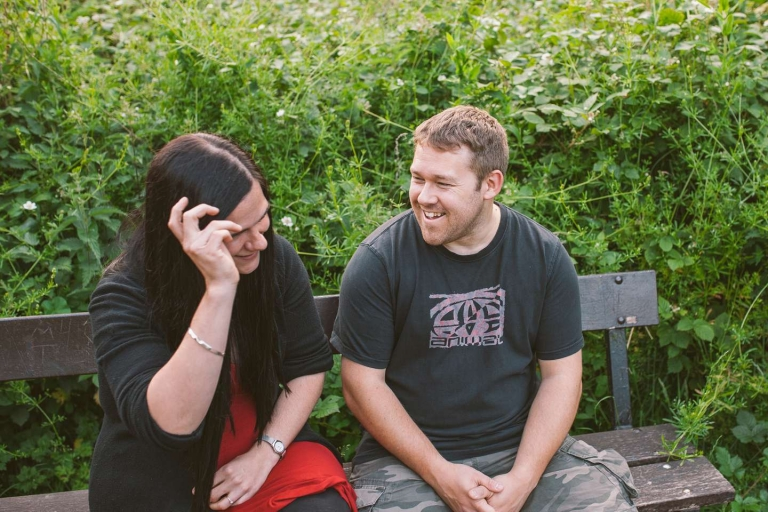 Couple laughing on bench during Watford park engagement shoot