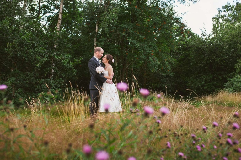Couple embrace amongst the grass and thistles opposite The Three Oaks