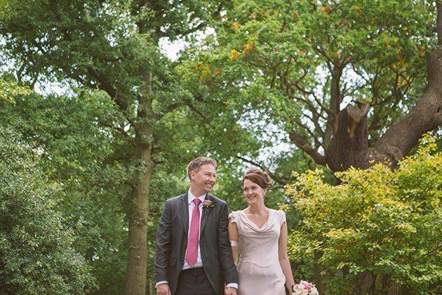 Bride and groom walk along path at Pembroke Lodge