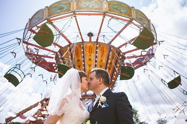 Bride and groom stood by funfair at Watford village hall wedding