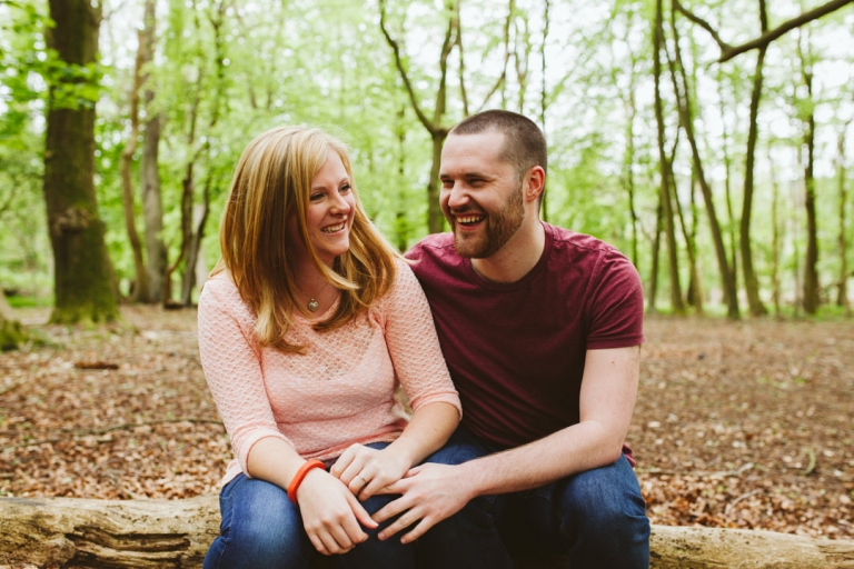 Engaged couple laughing whilst sat on log in woods