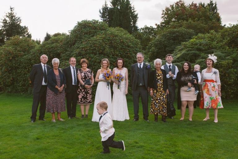 Pageboy running past group shot at Shendish Manor wedding