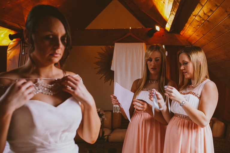 Bridesmaids looking at instructions for garter at South Farm wedding