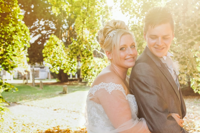 Hitchin Wedding of couple by St Marys Church in sunlight during natural wedding photography