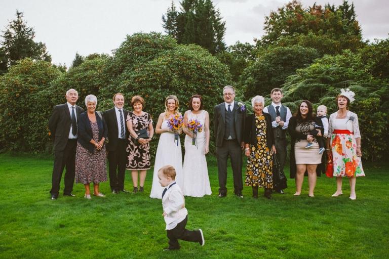 Pageboy runs past group shot at Shendish Manor wedding