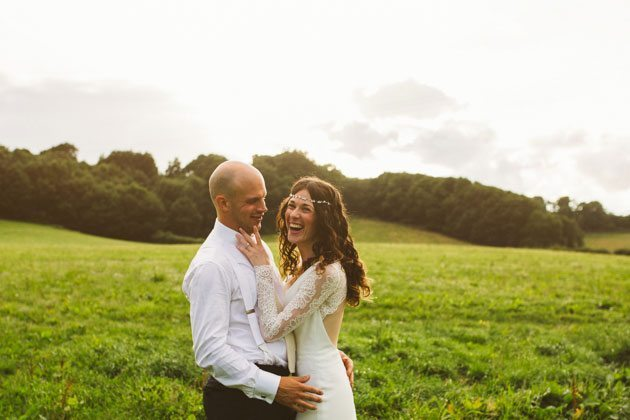 Bride and groom laughing in field during Gate Street Barn wedding
