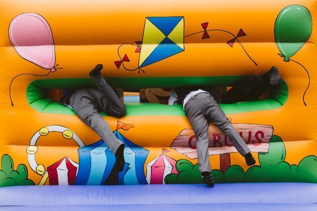Kids squeezing through bouncy castle at Tewin Bury wedding