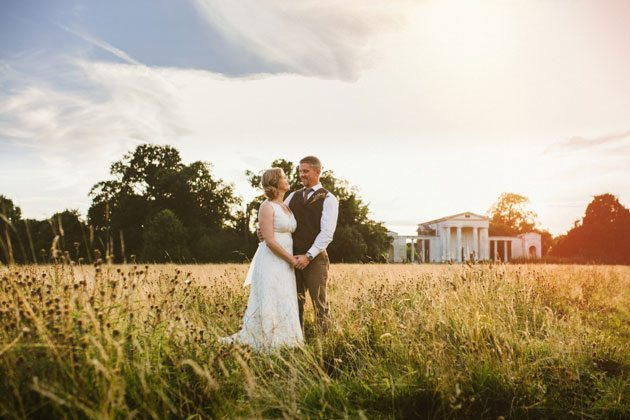 Bride and groom stood in field by Palladian Church in Welwyn at sunset