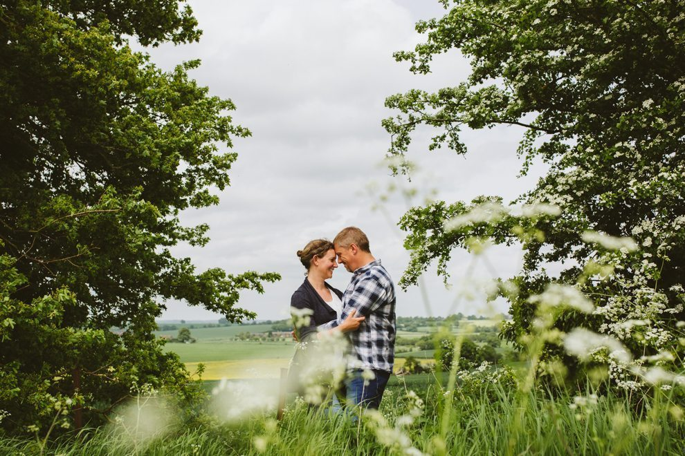 Couple embrace during Welwyn engagement shoot amongst the flowers