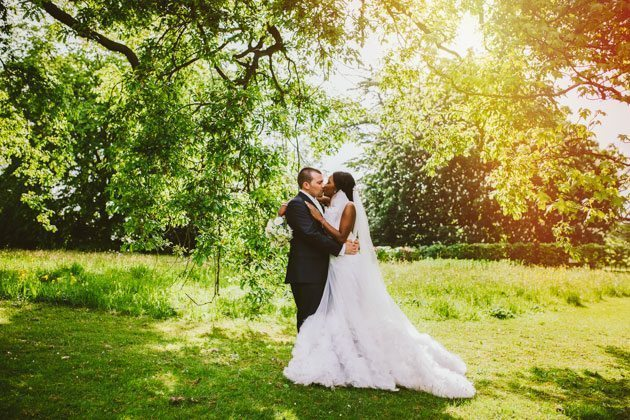 Groom and bride kiss in the sunlight within the gardens of Woburn Sculpture Gallery during their wedding