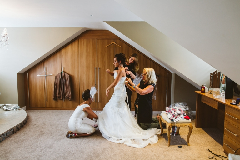 Tewin Bury Farm Wedding - bride being helped into dress - wedding day timings