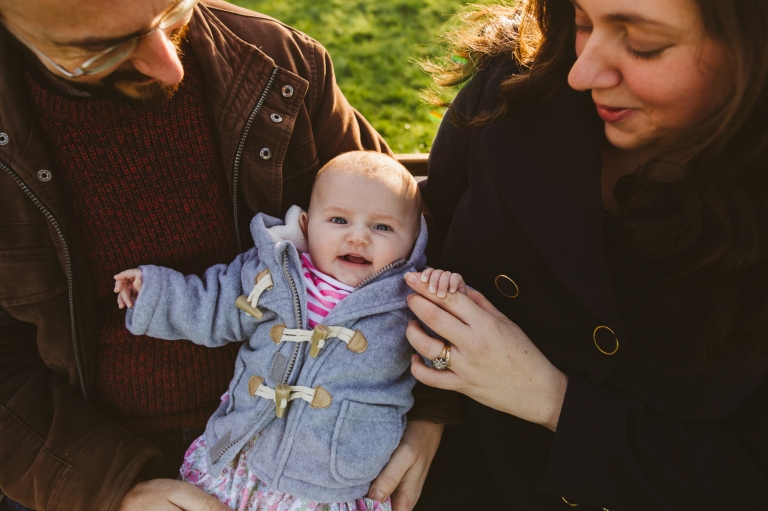 Baby Photoshoot Buckinghamshire - baby hugged by parents on bench