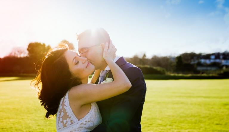 Wedding Photographer Hertfordshire - groom kisses bride at North Middlesex Cricket Club wedding