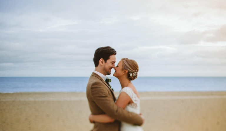 Wedding Photographer Hertfordshire - Groom and bride hug on beach by The Sandbanks Hotel in Poole