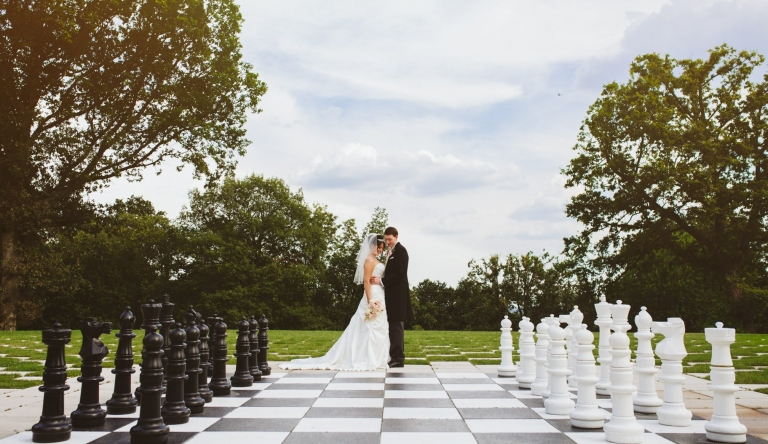 Bride and groom on chess board at Laura Ashley The Manor in Hertfordshire