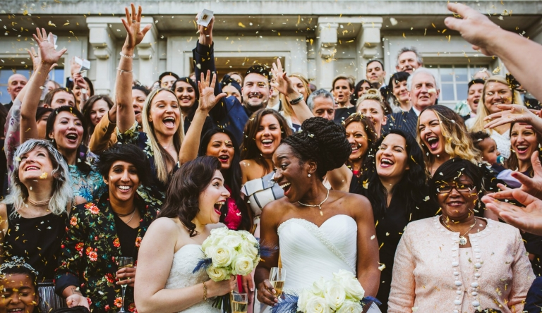 Wedding Photographer Hertfordshire - Confetti thrown at two brides on steps of Hackney Town Hall during wedding