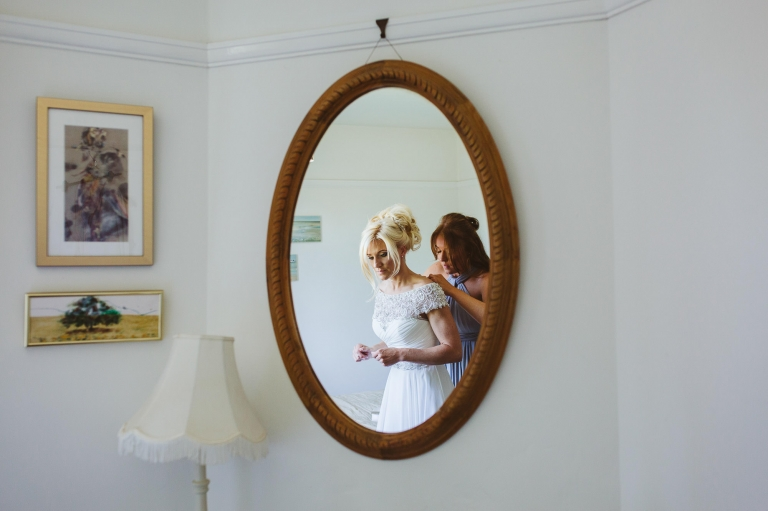 Bride's reflection in mirror as she gets into her wedding dress