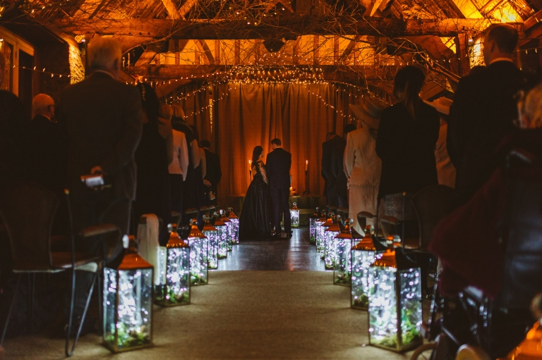 Dark winter wedding ceremony with candlelights at The Tythe Barn