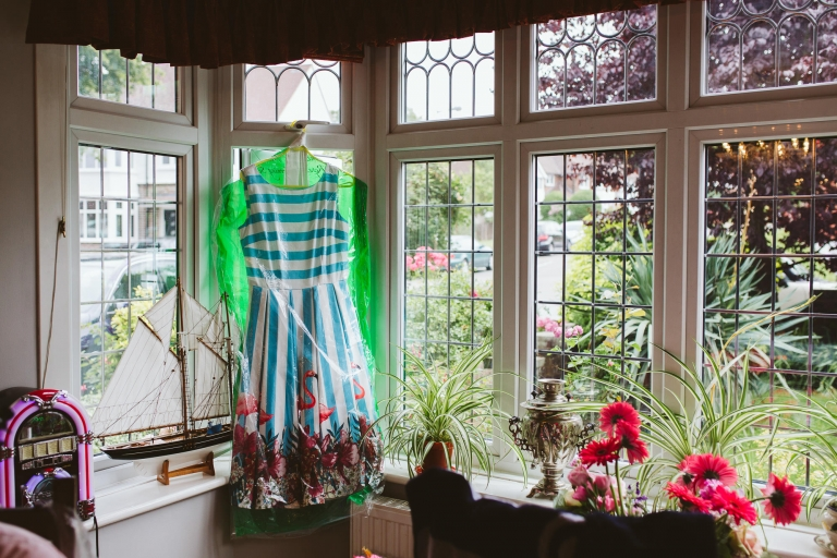 Collectif Clothing Flamingo dress hung up on window for bridesmaid