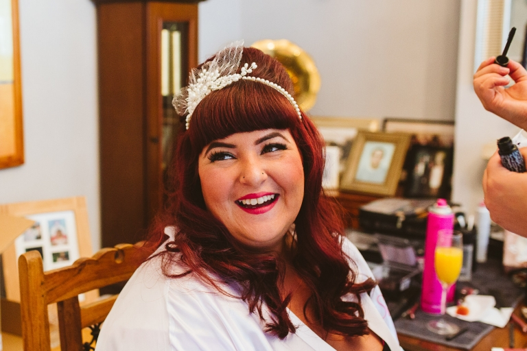 Bride smiling as she gets ready for her wedding in Enfield