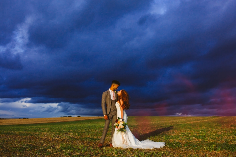 Groom and bride stood against storm sky with smokebomb at Tip Top Venues in best of 2017 wedding photography