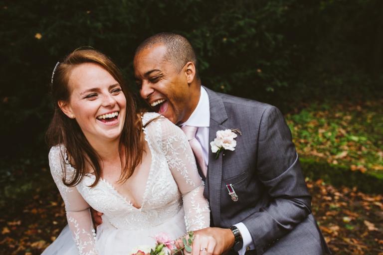 Bride and groom laugh in gardens of Hunton Park