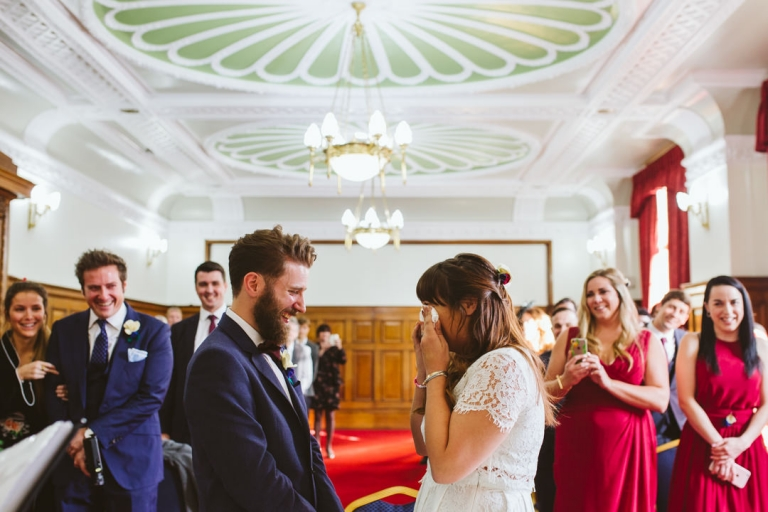 Bride wipes eyes as groom laughs during Islington Town Hall wedding ceremony