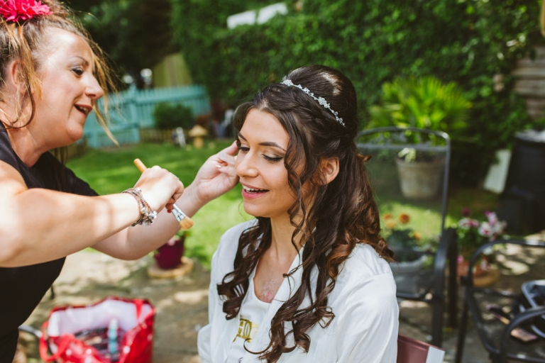 Bride smiles as she has her makeup done in her parents' garden