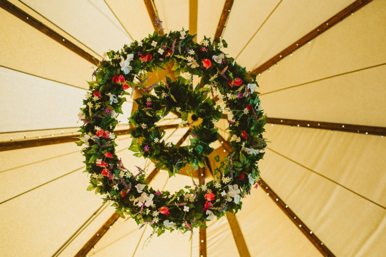Flower chandelier hanging from tipi by Timber and Canvas Tipi Hire