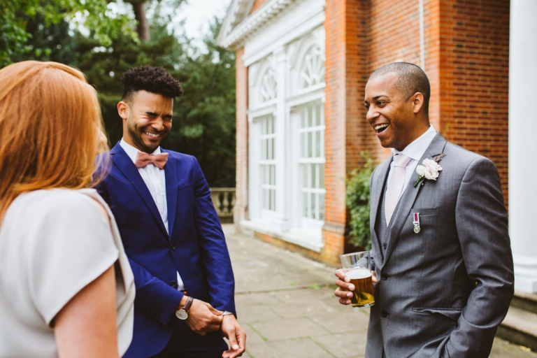 Groom laughing with guests before wedding ceremony at Hunton Park