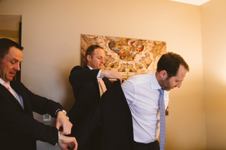 Best man helps groom into suit jacket for Gate Street Barn wedding