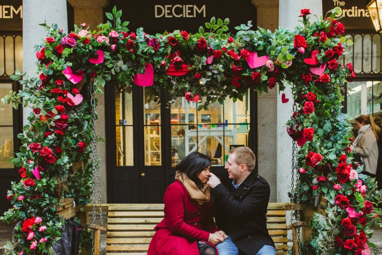 Groom to be bops bride to be's nose on bench in Covent Garden
