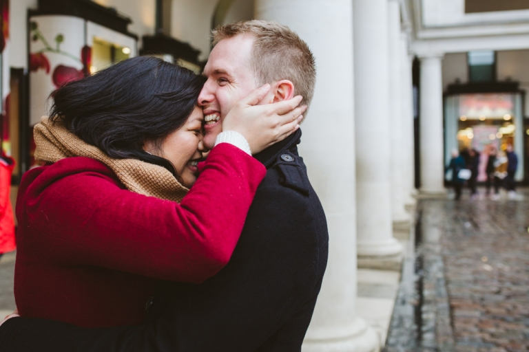 Couple squish together during rainy engagement shoot