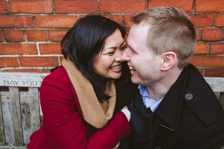 Couple snuggle up during rainy engagement shoot