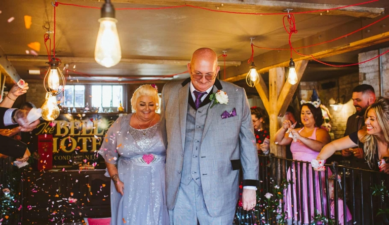 Bride and groom do red carpet walk at The Bell in Ticehurst by Hertfordshire wedding photographer Clare Tam-Im