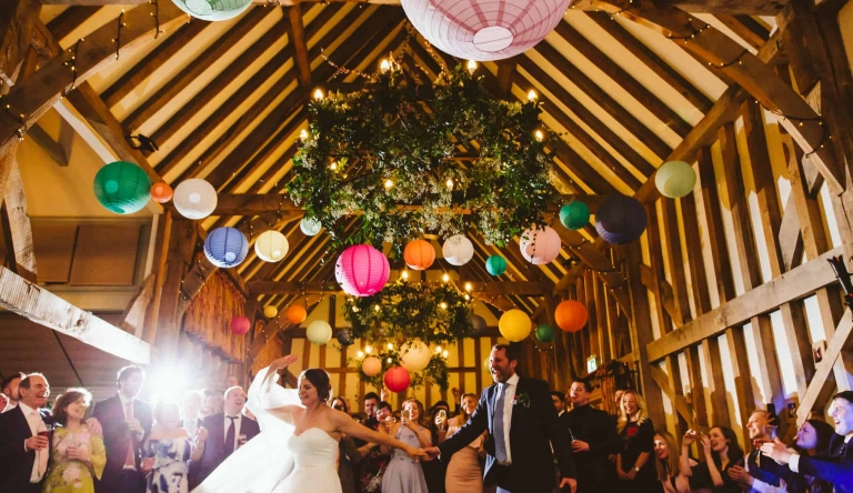 Bride and groom dance under colourful hanging lanterns at Gate Street Barn by Hertfordshire wedding photographer Clare Tam-Im