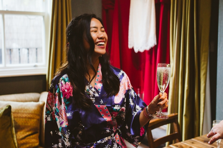 Bridesmaid laughs whilst holding a glass of champagne