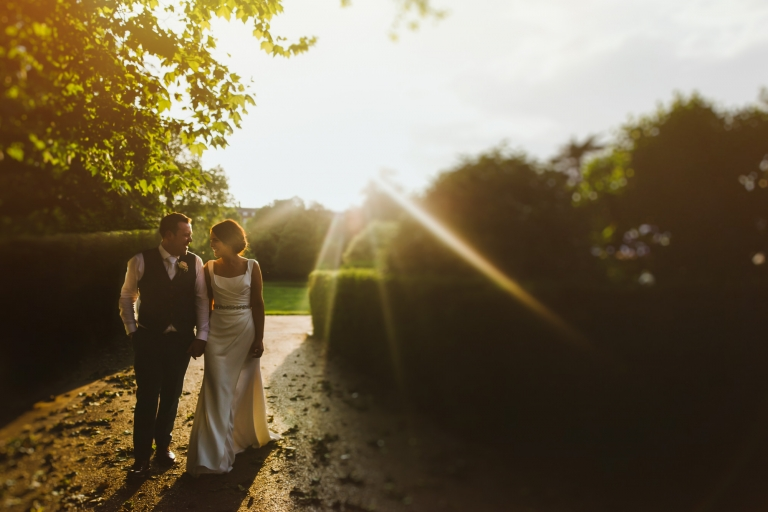 Bride and groom walking together at sunset at The Hurlingham Club