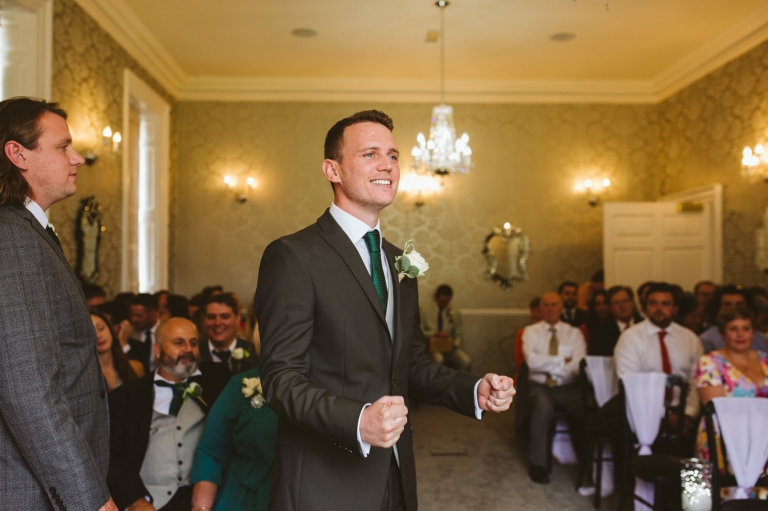 Excited groom waiting for bride to arrive for wedding ceremony